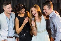 Amis heureux chantant des chansons ensemble Images stock
