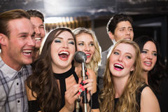 Amis heureux chantant le karaoke ensemble Photo stock