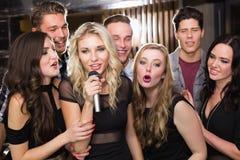 Amis heureux chantant le karaoke ensemble Images libres de droits