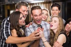 Amis heureux chantant le karaoke ensemble Photos libres de droits