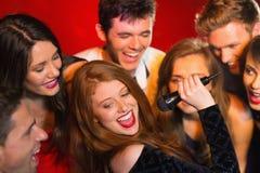 Amis heureux chantant le karaoke ensemble Photographie stock libre de droits