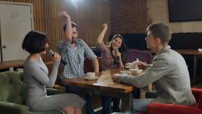 Amis heureux chantant le karaoke ensemble dans une barre Image stock