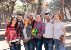 Amis heureux chassant la boule dehors Photos stock
