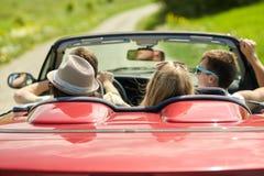 Amis heureux conduisant dans la voiture convertible à l'été Photo stock