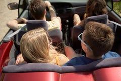 Amis heureux conduisant dans la voiture convertible à l'été Images libres de droits