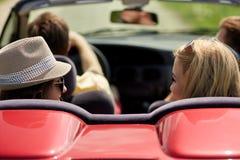 Amis heureux conduisant dans la voiture convertible à l'été Image stock
