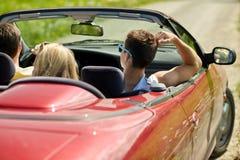 Amis heureux conduisant dans la voiture convertible à l'été Photographie stock