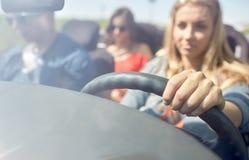 Amis heureux conduisant dans la voiture convertible Image libre de droits