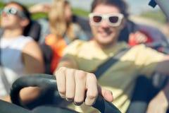 Amis heureux conduisant dans la voiture convertible Photos libres de droits