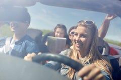 Amis heureux conduisant dans la voiture de cabriolet Photo stock