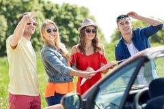 Amis heureux conduisant dans la voiture de cabriolet Images stock
