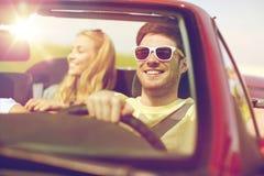 Amis heureux conduisant dans la voiture de cabriolet Photographie stock