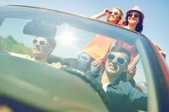 Amis heureux conduisant dans la voiture de cabriolet Image libre de droits