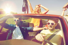 Amis heureux conduisant dans la voiture de cabriolet Photos stock