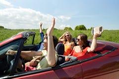 Amis heureux conduisant dans la voiture de cabriolet au pays Photos libres de droits