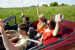 Amis heureux conduisant dans la voiture de cabriolet au pays Photo stock