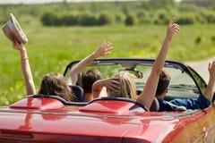 Amis heureux conduisant dans la voiture de cabriolet au pays Image libre de droits