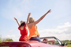 Amis heureux conduisant dans la voiture de cabriolet au pays Image stock