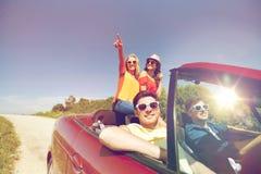 Amis heureux conduisant dans la voiture de cabriolet au pays Photographie stock