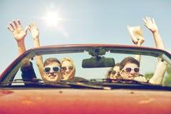 Amis heureux conduisant dans la voiture de cabriolet au pays Photographie stock libre de droits