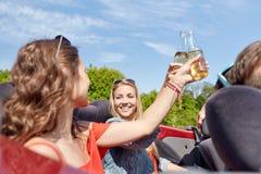 Amis heureux conduisant dans la voiture de cabriolet avec de la bière Photos stock