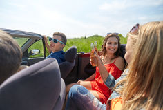 Amis heureux conduisant dans la voiture de cabriolet avec de la bière Photos libres de droits