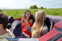 Amis heureux conduisant dans la voiture de cabriolet avec de la bière Photographie stock libre de droits