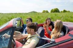 Amis heureux conduisant dans la voiture de cabriolet avec de la bière Image libre de droits