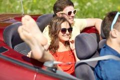 Amis heureux conduisant dans la voiture de cabriolet dehors Photographie stock libre de droits