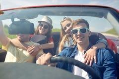 Amis heureux conduisant dans la voiture de cabriolet dehors Images libres de droits