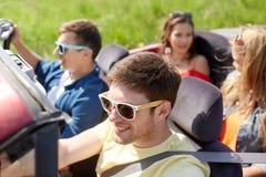 Amis heureux conduisant dans la voiture de cabriolet dehors Images stock