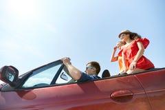 Amis heureux conduisant dans la voiture de cabriolet dehors Photographie stock