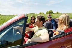 Amis heureux conduisant dans la voiture et parler de cabriolet Photo libre de droits