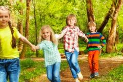Amis heureux courant dans la forêt tenant des mains Images libres de droits