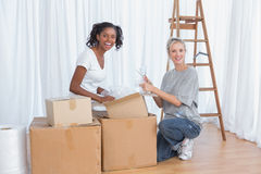Amis heureux déballant des boîtes dans la nouvelle maison Photographie stock libre de droits