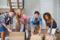 Amis heureux déballant des boîtes dans la nouvelle maison Photo libre de droits
