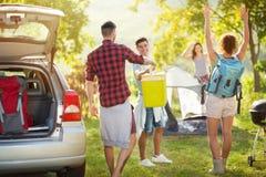 Amis heureux déballant la voiture pour des vacances en camping Image libre de droits