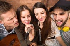 Amis heureux dépensant leur karaoke de chant de temps gratuit Photo stock