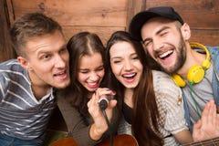 Amis heureux dépensant leur karaoke de chant de temps gratuit Image stock