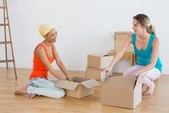 Amis heureux déroulant des boîtes dans une nouvelle maison Photo libre de droits
