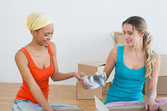 Amis heureux déroulant des boîtes dans une nouvelle maison Photographie stock libre de droits