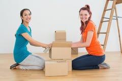 Amis heureux déroulant des boîtes dans une nouvelle maison Photo stock