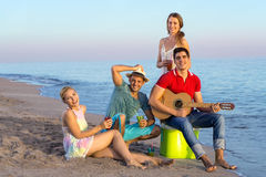 Amis heureux détendant à la plage Photographie stock libre de droits