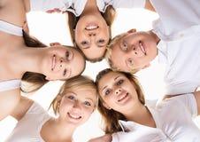 Amis heureux détendant ensemble sur le blanc Image stock