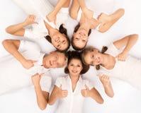 Amis heureux détendant ensemble sur le blanc Photographie stock