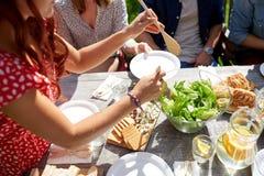Amis heureux dînant à la partie d'été Photo stock