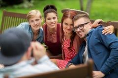 Amis heureux dînant à la réception en plein air d'été Photo stock