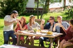 Amis heureux dînant à la réception en plein air d'été Photos libres de droits