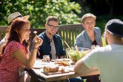 Amis heureux dînant à la réception en plein air d'été Image libre de droits