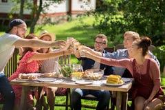 Amis heureux dînant à la réception en plein air d'été Images libres de droits
